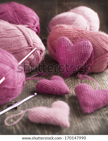 Crochet pink hearts  and yarn on wooden background. Selective fo - stock photo