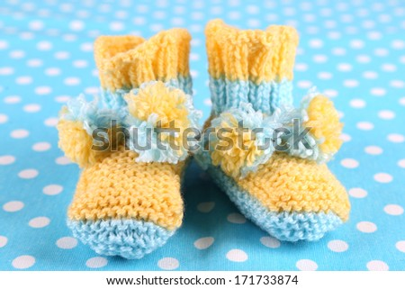 Crocheted booties for baby, on color background - stock photo