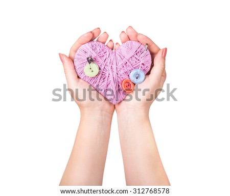 crocheted heart in hand isolated on white - stock photo