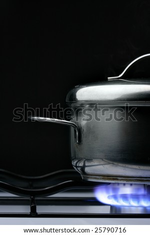 Crock on the gas stove over black background - stock photo