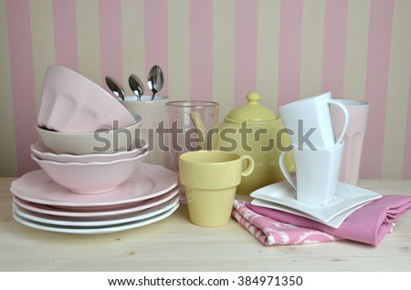 Crockery in pink, yellow and white color on kitchen desk with striped wall in background - stock photo