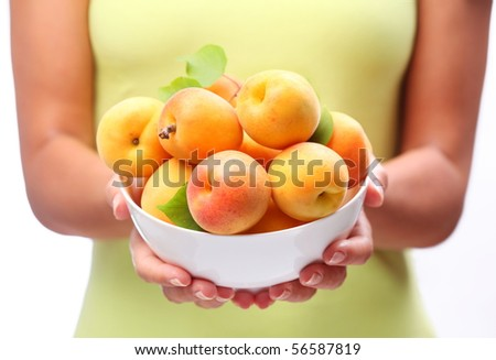 Crockery with ripe apricots in woman hands.