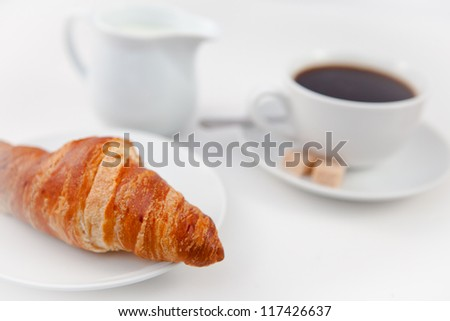 Croissant and a cup of coffee on white plates with sugar and milk against a white background