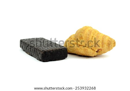 croissant and chocolate wafer candy on a white background - stock photo