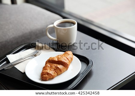 croissant and coffee in coffee shop - stock photo