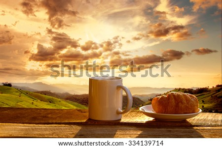 Croissant and coffee with mountain at morning sunrise. - stock photo