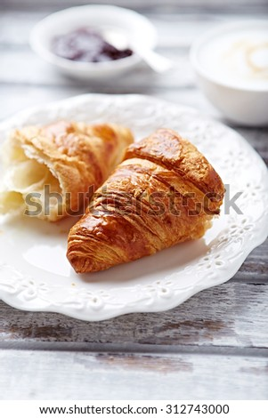 Croissant, cappuccino and cherry jam    - stock photo