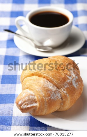 Croissant in white plate and white cup of black coffee on blue checkered tablecloth.