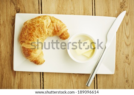 Croissant pastry on white dish and wooden table top - stock photo