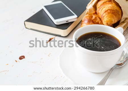 Croissant sandwich with ham, cheese and arugula, coffee, phone, notepad, white wood background - stock photo