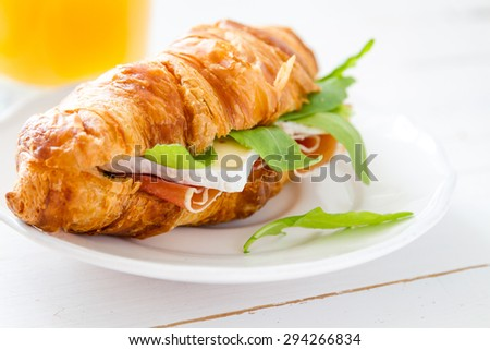 Croissant sandwich with ham, cheese and arugula, white wood background - stock photo