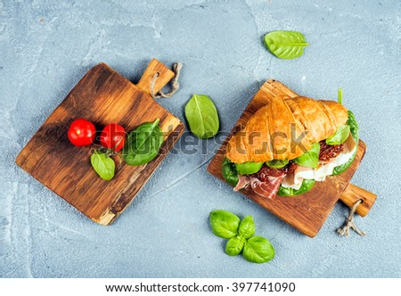Croissant sandwich with smoked meat Prosciutto di Parma, sun dried tomatoes, fresh spinach and basil on small rustic wooden boards over stone textured grey background, top view - stock photo