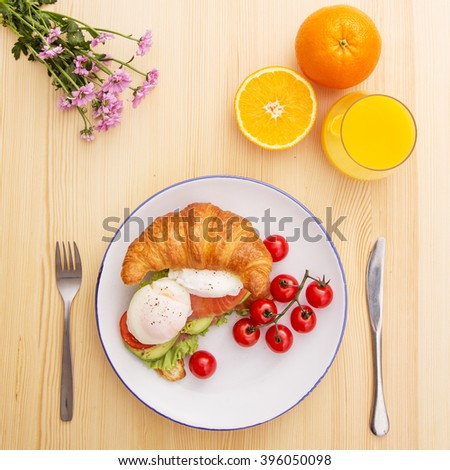 Croissant with fish, poached eggs and vegetables - stock photo