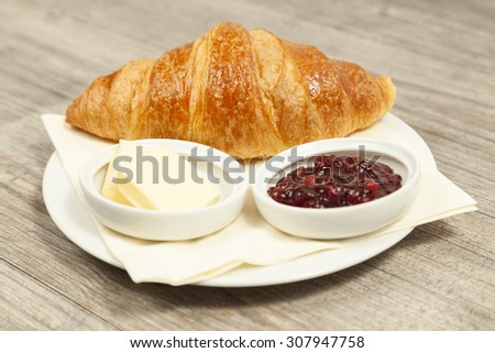 Croissant with jam and butter - stock photo