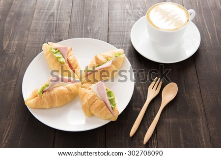 Croissant with parma ham and coffee on wooden table. - stock photo
