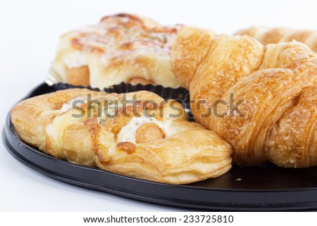 Croissants and danish pastries on a black tray. - stock photo