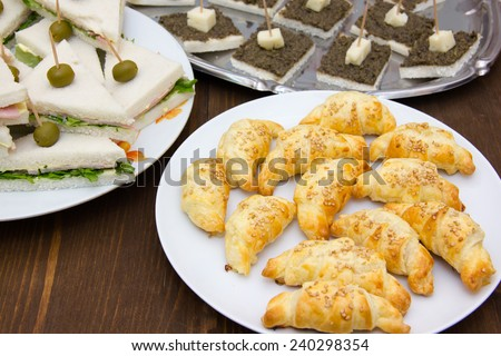 Croissants and other appetizers on wooden table seen up close