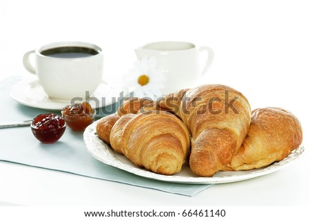 croissants,marmalades and coffee on a light blue table cloth