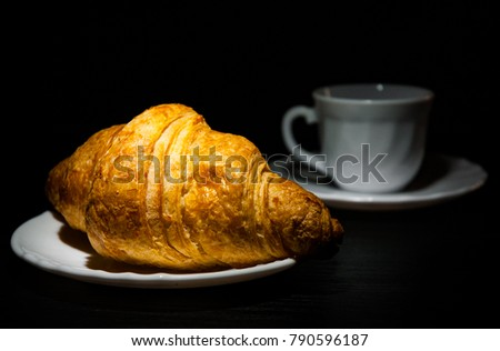 croissants on plate and cup of tea or coffee on dark wooden background