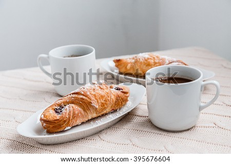 croissants on white plates and coffee shop in a white cup on a white background