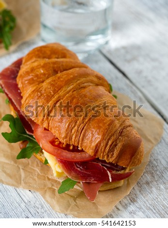 croissants with argugula, jamon, cheese and tomato on wooden surface