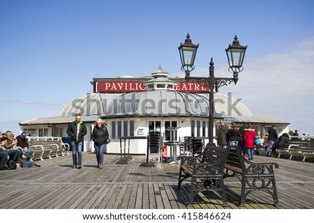Cromer, UK - April 6 2016:  People walking at sitting on the pier at Cromer on a sunny day - stock photo