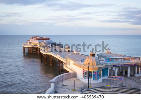 Cromer, UK - April 6 2016:  The pier in Cromer, Norfolk in the late afternoon, at high tide. - stock photo