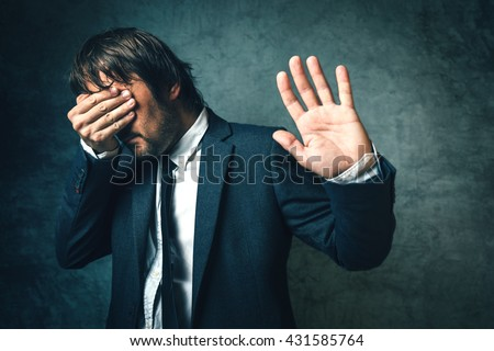 Crooked politician hiding face from newspaper photographers after political scandal,  public embarrassment, hand gesturing stop sign - stock photo