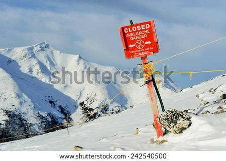 Crooked Red Avalanche Sign in Canadian Rockies - stock photo