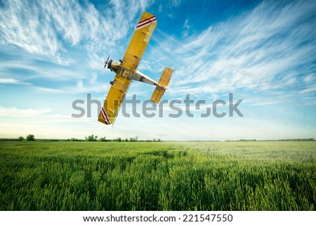 crop duster airplane flies low over a wheat field spraying fungicide and pesticide - stock photo