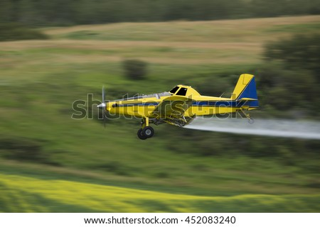 Crop duster spraying a crop, taken using a Panning Technique with motion blur. - stock photo