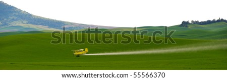 Crop dusting airplane spraying pesticide on wheat fields in the Palousezf - stock photo
