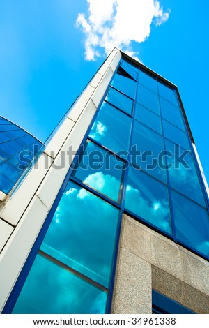 Crop of blue glass wall of skyscraper with sky?s reflection on it
