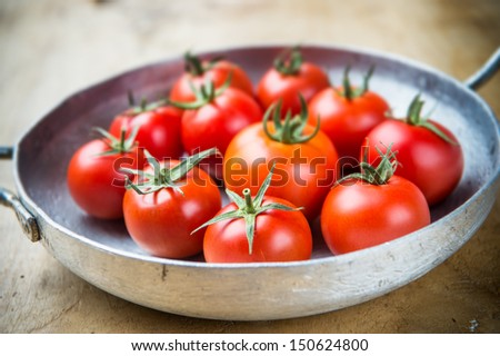 Crop of young tomatoes in a metal skillet, rustic style