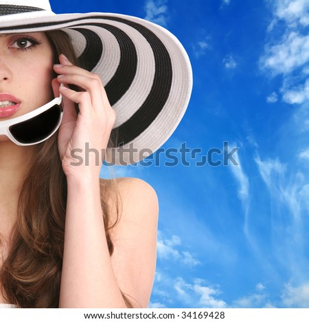 crop portrait of the beautiful girl in striped hat and sunglasses on background blue sky - stock photo