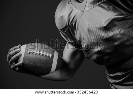 Cropped American football player holding ball against black - stock photo