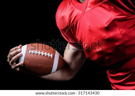 Cropped American football player holding ball against black background - stock photo