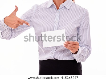 Cropped businesswoman, wearing a button down shirt, holding a blank copy space in one hand pointing at the copy space with the other hand