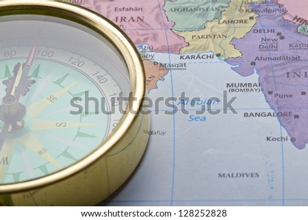 Cropped close up image of compass on map - stock photo