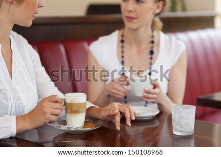 Cropped close up view of two young woman drinking coffee in a restaurant or cafe - stock photo