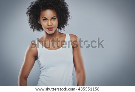 Cropped front view on beautiful young tough Black woman in white sleeveless undershirt and calm expression with vignette gray background and copy space - stock photo