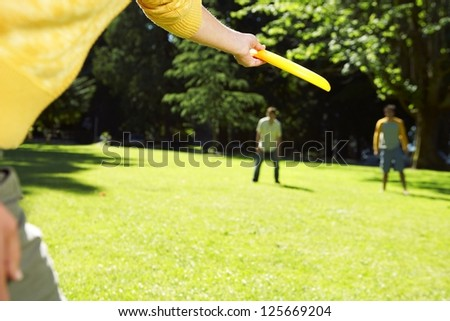 cropped hand in the foreground about to throw a frisbee to two people at the background, with trees in the background - stock photo