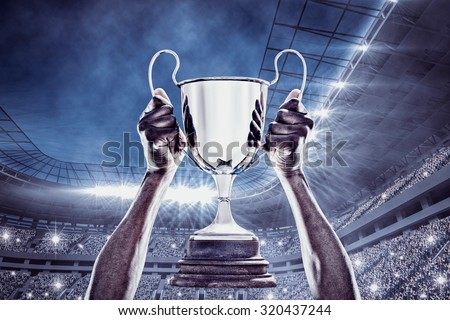 Cropped hand of athlete holding trophy against football stadium - stock photo