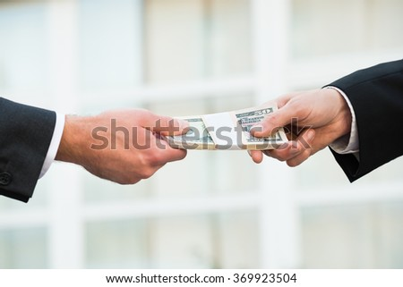 Cropped hand of businessman giving bribe to partner outdoors - stock photo