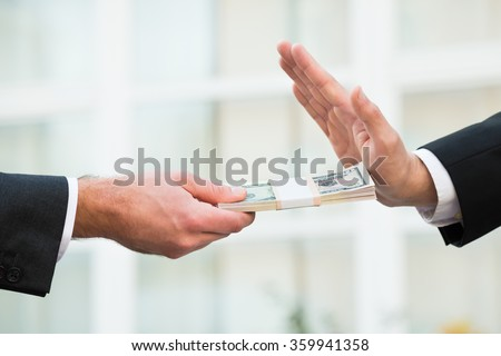 Cropped hand of businessman refusing to take bribe from partner outdoors - stock photo