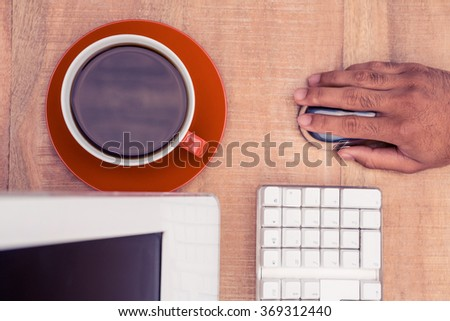Cropped hand of businessman using mouse while working at table in office - stock photo