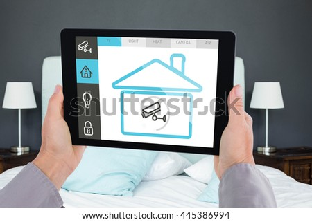 Cropped hand of man holding digital tablet against view of a bed and night stands