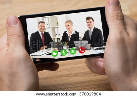 Cropped hands of businessman video conferencing with colleagues on smartphone at desk - stock photo
