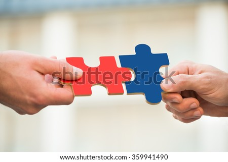 Cropped hands of businessmen joining jigsaw pieces outdoors - stock photo