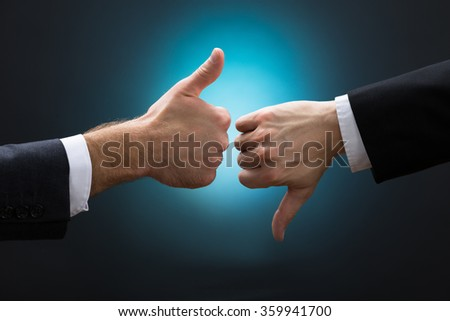 Cropped hands of businessmen showing like and dislike signs against blue background - stock photo